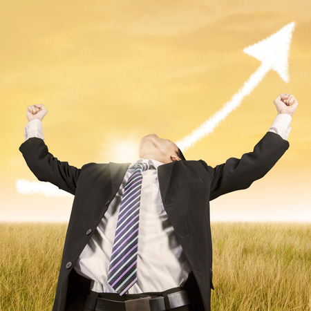 profit celebration: Young businessman wearing business suit at field and celebrate his winning under arrow upward
