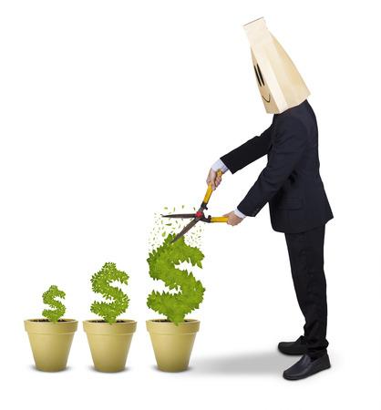 tijeras: Empresario de sexo masculino con la cabeza de cartón, utilizando unas tijeras para cortar el árbol del dinero, aislado en blanco