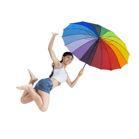 Cheerful woman enjoy freedom in the studio and jumping by holding a rainbow umbrella
