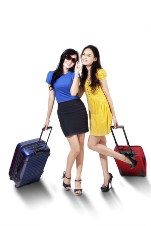 Portrait of two attractive female travelers standing in the studio while carrying suitcase
