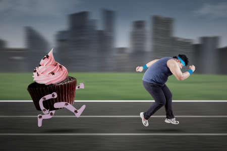 weight loss man: Overweight person exercising on track to lose weight and hallucinate chased by cupcake