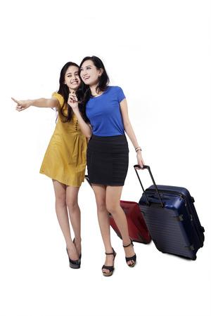 mujer con maleta: Retrato de muchachas alegres que caminan en el estudio, mientras que el transporte de equipaje y señalando algo Foto de archivo