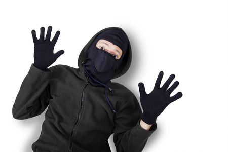 red handed: Closeup of male burglar wearing black mask and jacket, shot in studio with expression of caught and surrender