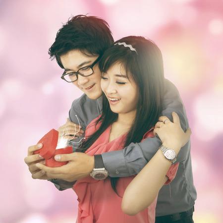 hombre romantico: Retrato de hombre rom�ntico dar un presente a su novia, tiro con luces de desenfocado Foto de archivo
