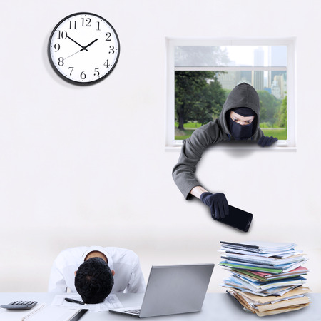 careless: Male robber with mask, stealing cellphone through a window with a careless man sleeping in office