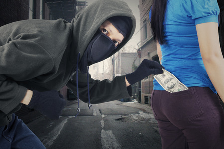 delincuencia: Retrato de ladrón masculina robó dinero de bolsillo de la víctima en la calle