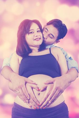 hacer el amor: Retrato de la mujer embarazada y su marido hacen símbolo de amor en el vientre, tiro con desenfoque de fondo Foto de archivo