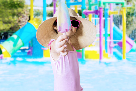 girl with camera: Attractive little girl showing ice cream on the camera while wearing swimsuit and hat at pool Stock Photo