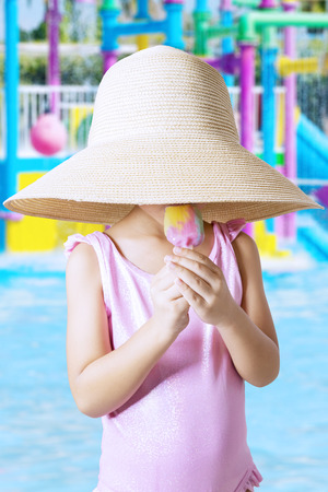little girl swimsuit: Little girl standing on the pool while wearing swimsuit and hat, eating ice cream