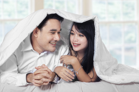 embracing couple: Happy couple look and smiling each other on bed under blanket at home Stock Photo