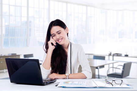 finance manager: Young female entrepreneur doing her job in the office while talking on the mobile phone