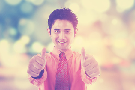 light worker: Young male worker showing thumbs up on the camera, shot over festive light background Stock Photo