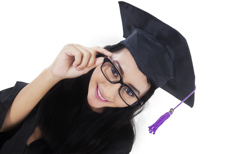 academic robe: High angle view of female graduate student smiling at the camera while wearing graduation gown Stock Photo