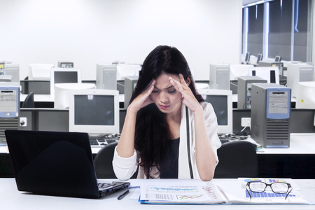 overwork: Young businesswoman working on table in office room and looks stressful