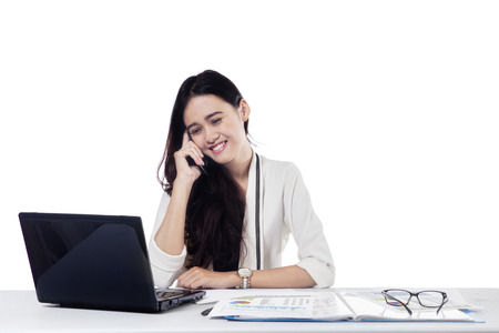 Portrait of young businesswoman working on the table with laptop while talking on the cellphone, isolated on white photo