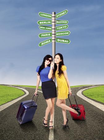 niñas chinas: Retrato de mujeres hermosas que se colocan en el camino con un poste indicador de destino del viaje