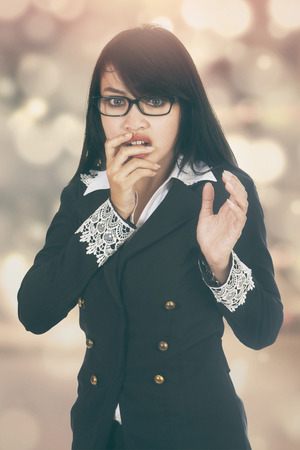 scolded: Portrait of young businesswoman looks scared, shot with festive light background