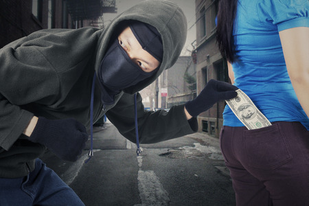 pickpocket: Portrait of male robber wearing mask and black jacket, stealing money from pocket of his victim at the street