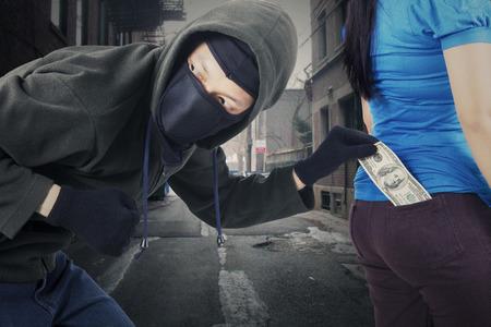 delincuencia: Retrato de ladrón masculino llevaba máscara y chaleco negro, robar dinero de bolsillo de la víctima en la calle