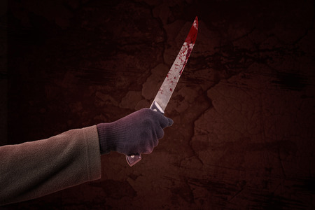 psycho: Closeup of psycho hand holding a sharp and bloody knife