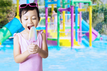 child swimsuit: Closeup of beautiful little girl wearing bikini at pool while eating ice cream Stock Photo