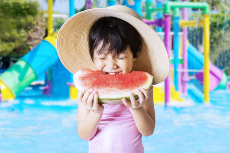 pink bikini: Lovely asian little girl wearing a big hat and swimwear at pool while eating a watermelon Stock Photo
