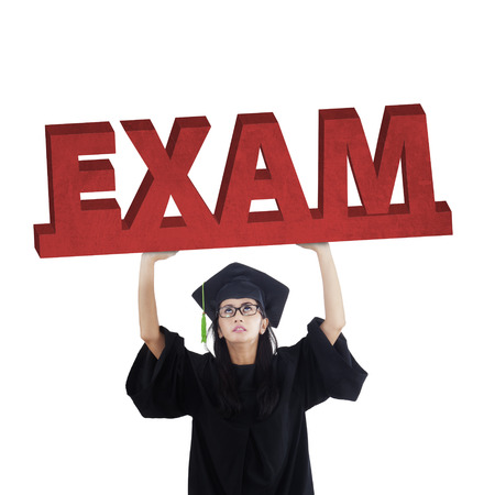 examination stress: Female graduate student standing in the studio while holding an exam text, symbolizing an exam pressure Stock Photo