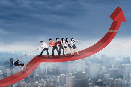 jovenes empresarios: Grupo de j�venes empresarios intenta subir y tirando de un gr�fico financiero hacia arriba Foto de archivo