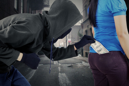 pickpocket: Male burglar in action to stole money while wearing black jacket, mask, and gloves