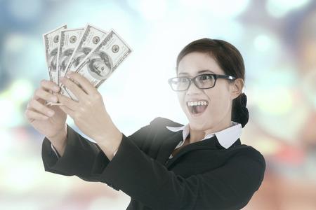indonesian woman: Portrait of happy businesswoman holding money dollars, shot against bokeh background
