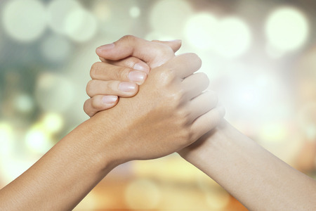 support group: Closeup of two hands joining together, symbolizing to trust each other, shot with a bokeh background