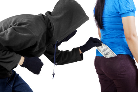 Male pickpocket taking money from pocket of woman while wearing black jacket and mask Stock Photo