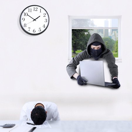 through the window: Male thief wearing mask and stealing a laptop in the office through a window when the employee is sleeping Stock Photo