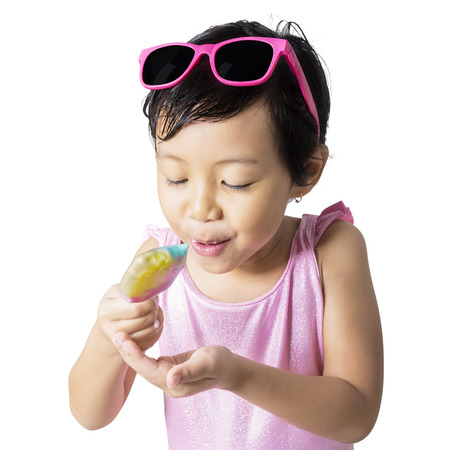 pink bikini: Portrait of little child wearing sunglasses and swimsuit with pink color, standing in the studio while eating a fresh ice cream Stock Photo