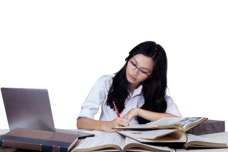 Portrait of nerdy schoolgirl studying with laptop and write quotations from textbooks, isolated on white photo