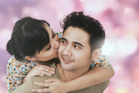 asian adult: Portrait of young girl kiss her boyfriend from the back, shot against bokeh background