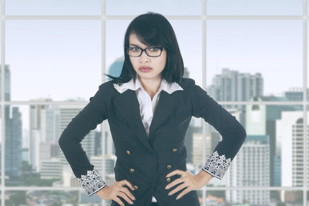bossy: Portrait of bossy businesswoman with hands on her waist and looking at the camera