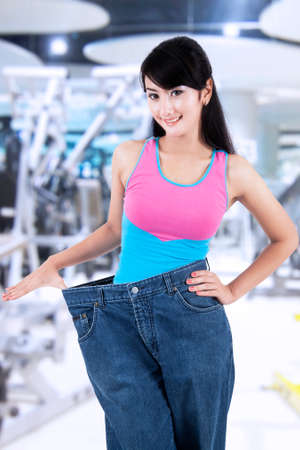 japanese woman: Portrait of successful woman lose her weight, standing at gym center with her old jeans Stock Photo