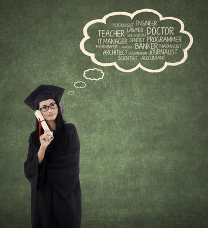 toga y birrete: Soltero joven hermosa imaginar sus futuros puestos de trabajo después de terminar su estudio mientras llevaba vestido de graduación