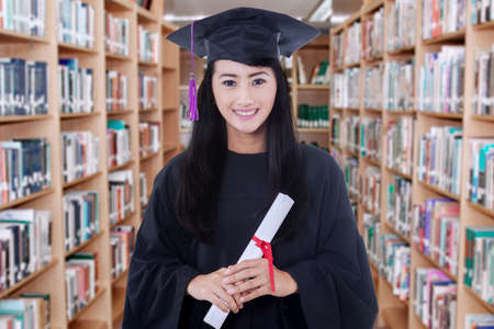 graduate: Portrait of female graduate student standing in the library while wearing graduation gown and holds a diploma