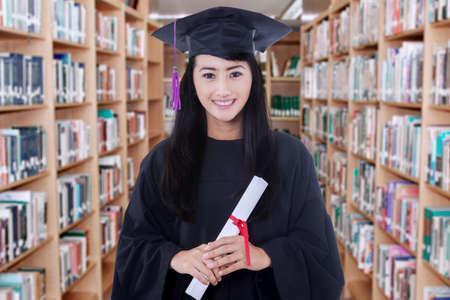 GRADUADO: Retrato del estudiante graduado femenino de pie en la biblioteca mientras llevaba vestido de graduación y tiene un diploma Foto de archivo