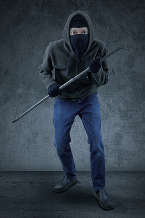 law breaker: Male mugger wearing black jacket and mask, ready to action while carrying a crowbar