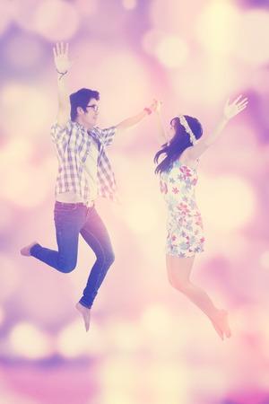 free background: Portrait of joyful couple enjoy freedom and jumping together, shot with festive blur background