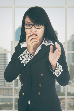 scolded: Portrait of female entrepreneur standing near the window and looks afraid