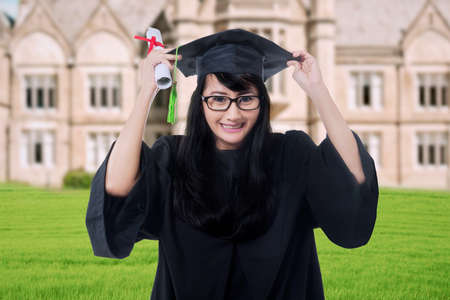 academic robe: Portrait of happy graduate student wearing graduation gown and hat, holding a diploma while celebrate graduation at schoolyard Stock Photo
