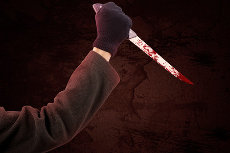 Closeup of hand using a sharp and bloody knife to stab and wounded Stock Photo