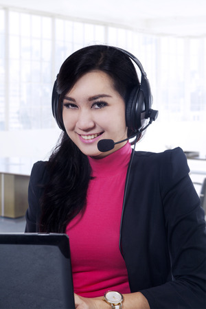 Portrait of pretty and friendly female call center operator, working in the office while smiling at the camera photo