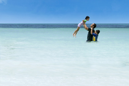 viaje familia: Retrato de hombre asiático que juega con sus hijos en la playa
