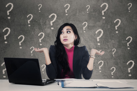 Beautiful businesswoman sitting in the office and looks confused with question marks on the background photo