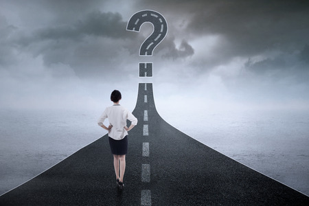 solves: Young female entrepreneur standing on the highway and look at a question mark